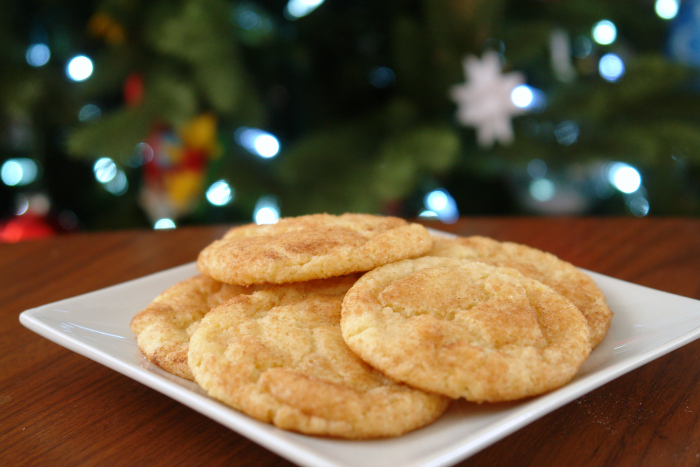 snickerdoodles on a plate in front of Christmas tree