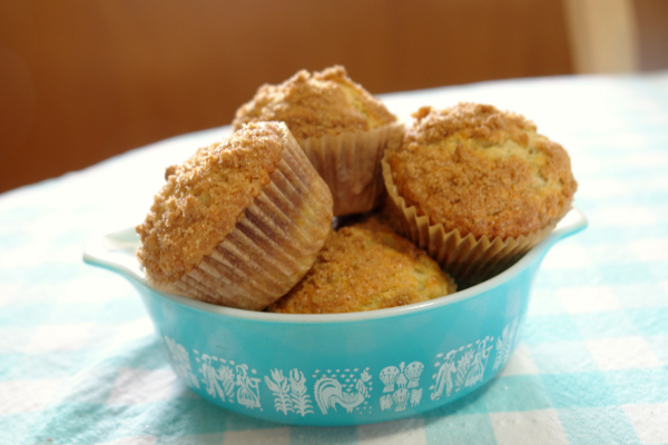 banana crumb muffins in a turquoise vintage Pyrex bowl on a table with an aqua table cloth
