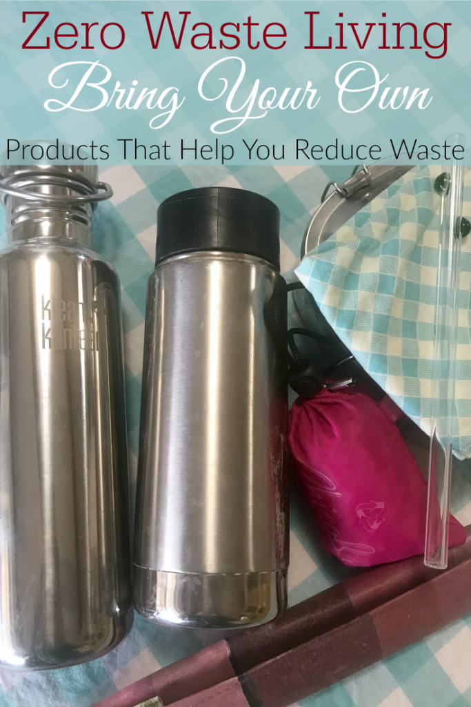 stainless steel water bottle and coffee mug, zero waste utensils, cloth napkin, reusable bag, glass straw on table