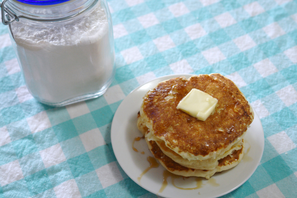 a stack of pancakes with butter and syrup, jar of pancake mix in background.