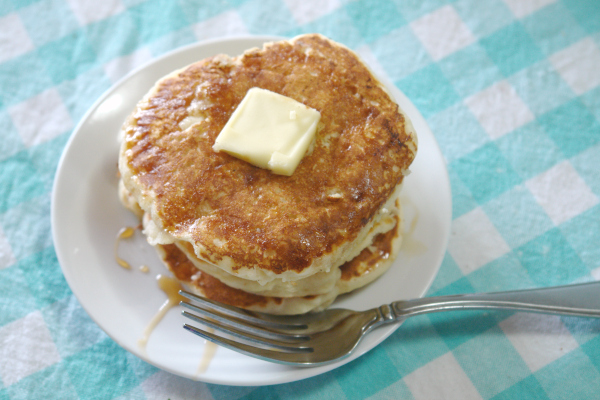 a stack of pancakes with butter and syrup