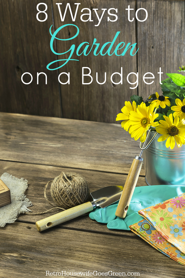 A bouquet of yellow bright garden flowers in a steel bucket and garden tools on a wooden background