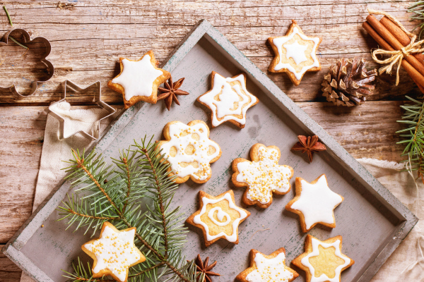 Assorted of Christmas cookies on wooden tray, served with Christmas tree branch over old table. Top view.