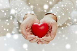 love, charity and people concept - close up of senior man with red heart in hands over snow