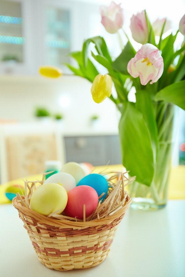 basket of brightly colored easter eggs on table with spring flowers