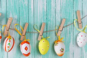 Colorful easter eggs in bucket and on clothes line on wooden background.