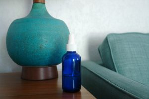 blue bottle of natural fabric refresher spray on table next to turquoise lamp and sofa