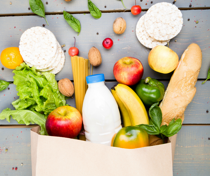 Grocery shopping concept. Different food in paper bag on wooden background.
