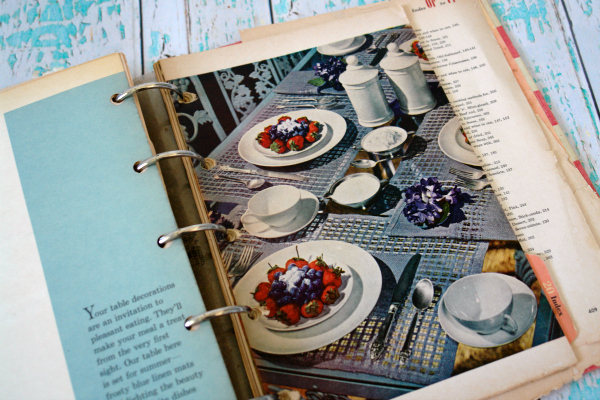 vintage cookbooks on white and aqua wooden background