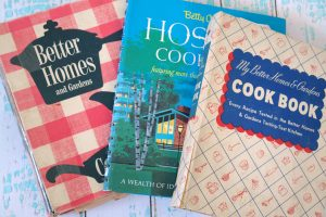 vintage cookbooks on white and aqua wooden background