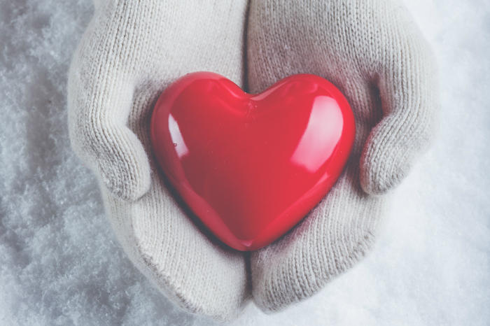 Hands in mittens holding a red heart.