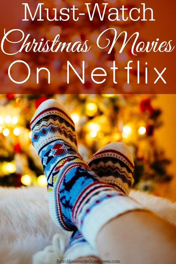 Feet in Christmas socks on sofa in front of tree