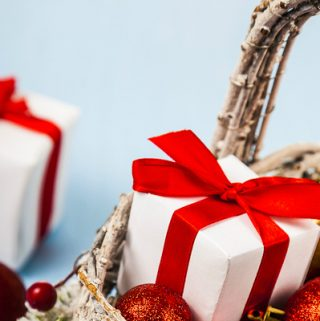 Gift basket with Christmas presents on a blue background.