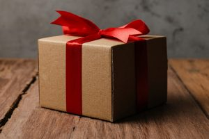Brown gift box with red ribbon and love shaped paper over rustic wooden table