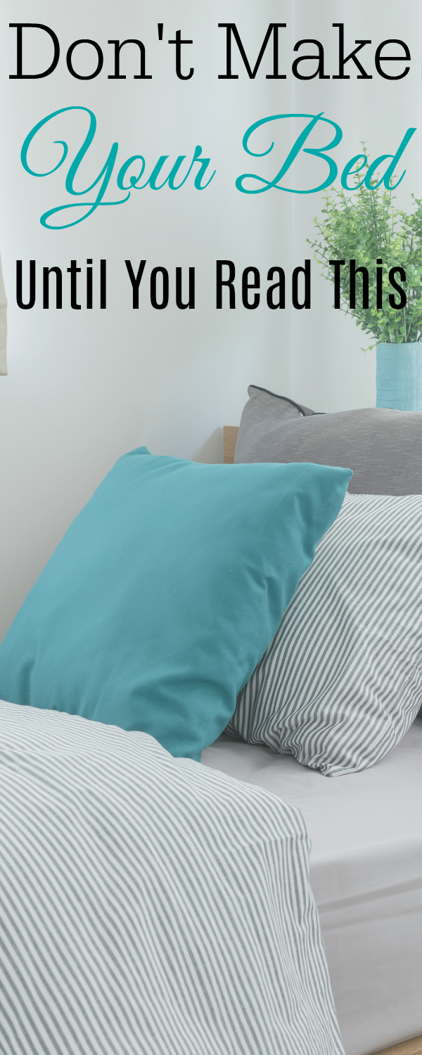 Made bed with grey and blue pillows