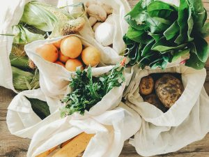 fresh vegetables in eco cotton bags on table in the kitchen.