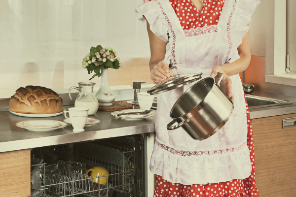 1950s Housewife loads the dishes in the dishwasher.
