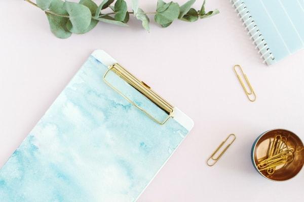 aqua clipboard, notebook and accessories on desk