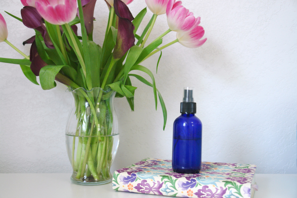 bottle spray bottle on floral journal with flowers in vase