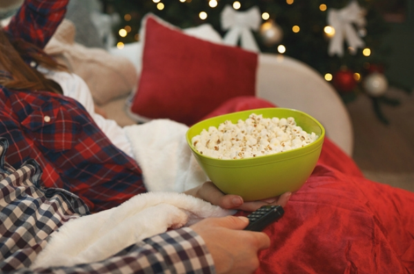 Couple at Christmas eating popcorn while watching tv
