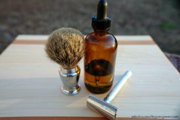 bottle of beard oil, shaving brush and razor on table outside