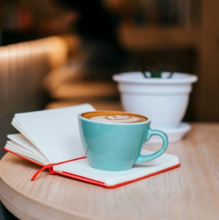 Blue cup of cappuccino with beautiful latte art and red notebook on the table with white fower pot.