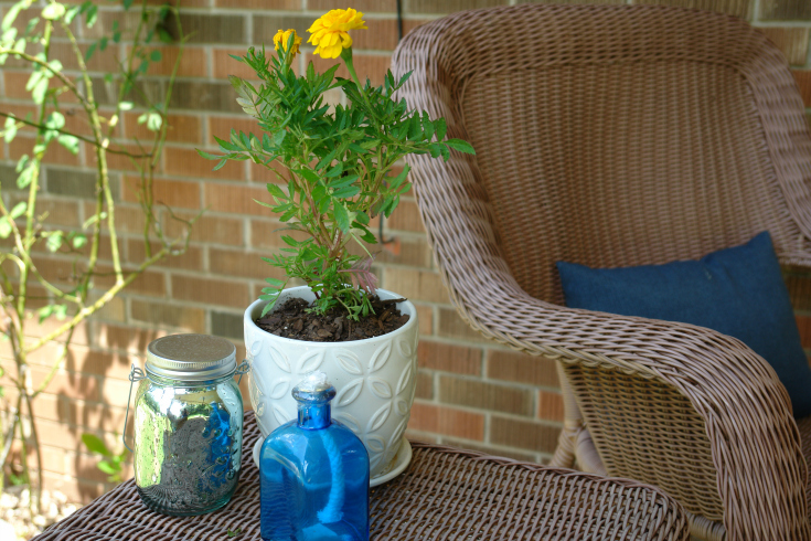 Chair and pillow, white pot with yellow flower, blue candle and blue mason jar