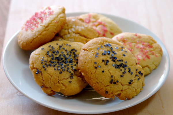 sugar cookies with colorful sprinkles on white plate
