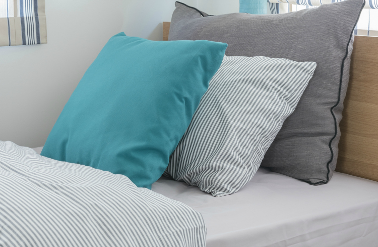 made bed with blue and grey pillows