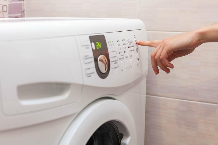 person starting washing machine