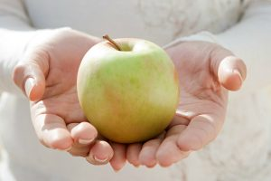 person holding a green apple