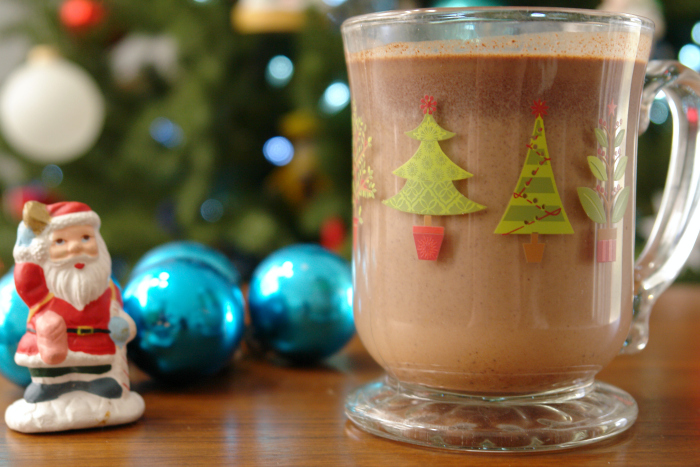 Hot Cocoa on table with Santa Claus figuring and blue ornaments