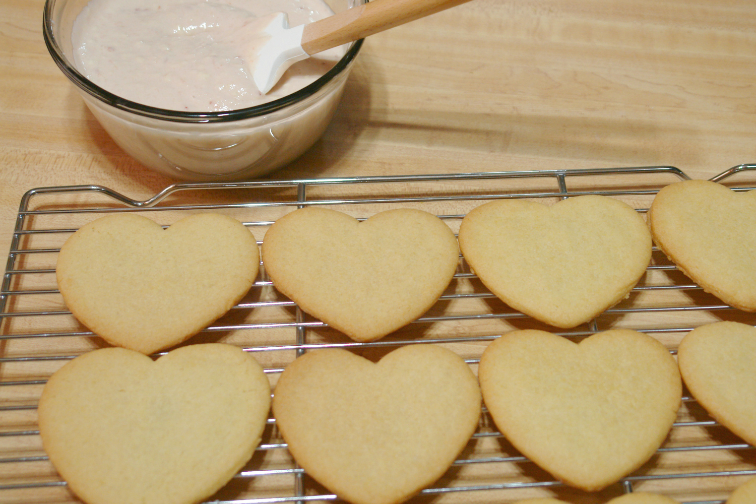 Sugar cookies cooling on cooling rack with a bowl of strawberry cream cheese frosting