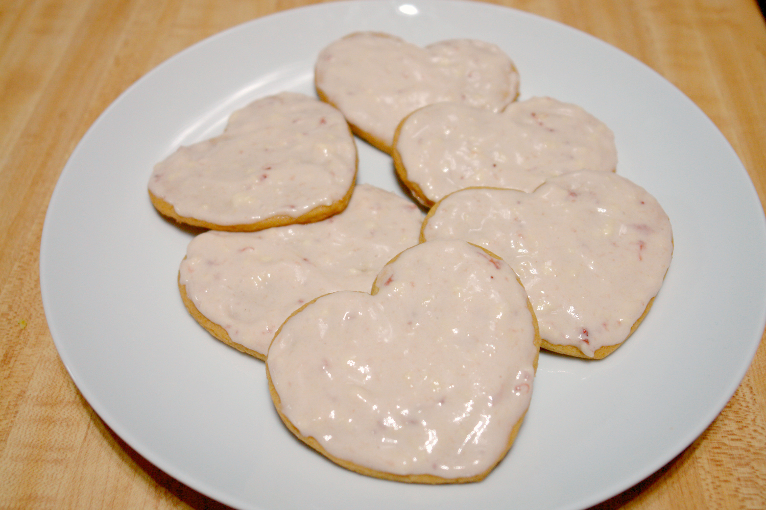 heart shaped sugar cookies with pink frosting on plate