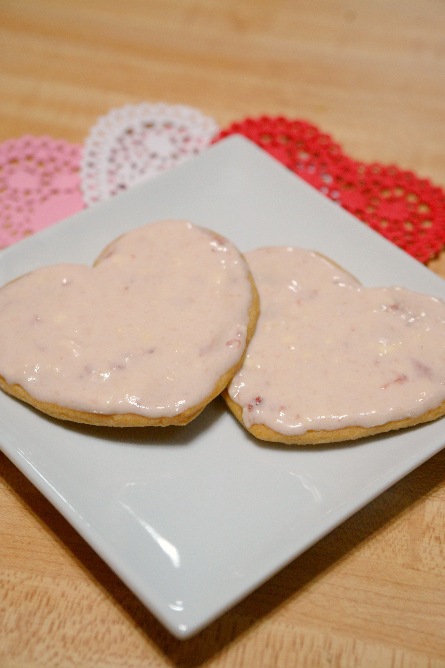 sugar cookies with strawberry cream cheese frosting on plates