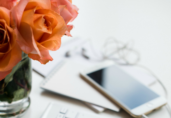 Bright white office table decor with fresh flowers, computer keyboard and smart phone.