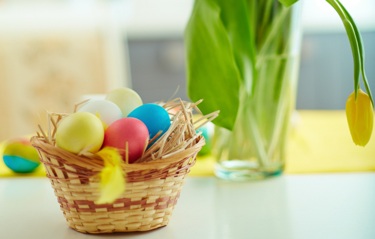 Easter basket with Easter eggs and tulips in the background