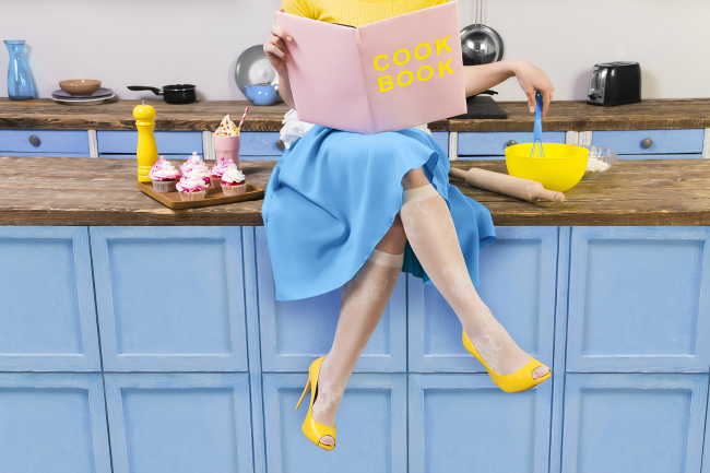 woman in retro dress sitting on counter with a cookbook and baking supplies