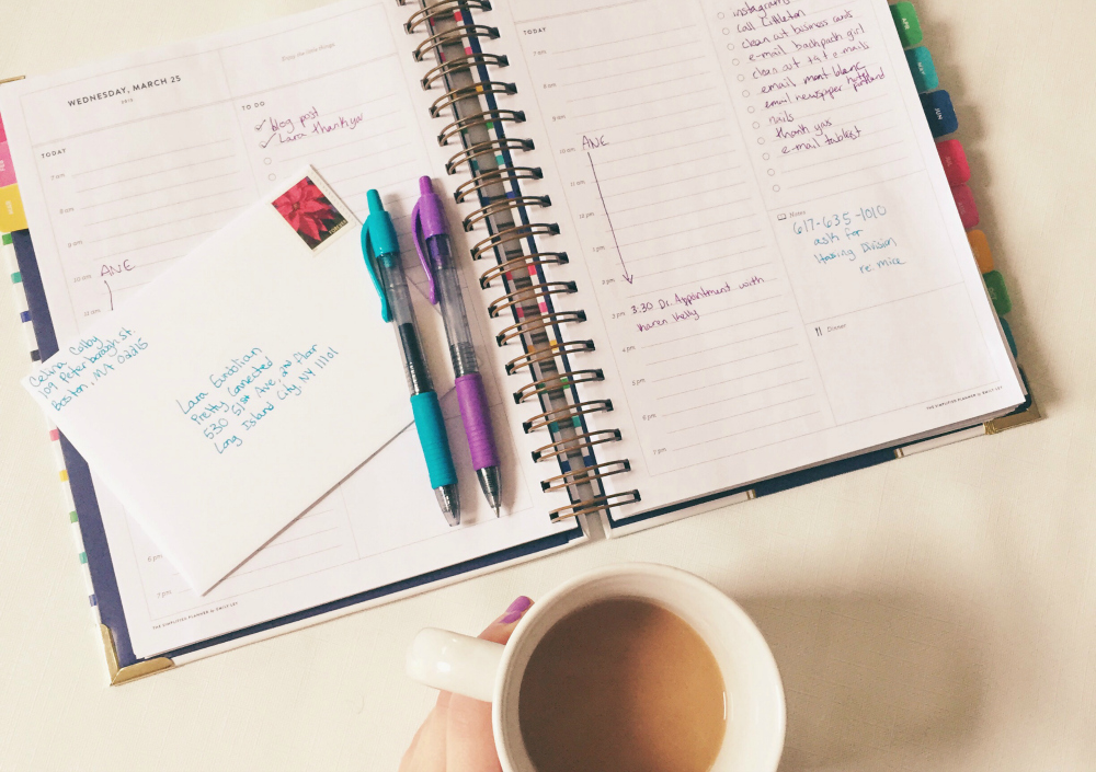 open planner on desk with pens and cup of coffee