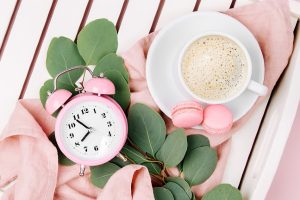Cup of coffee on white wooden serving tray with alarm clock and eucalyptus branch.