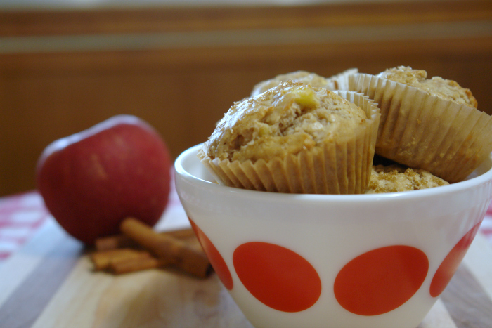 bowl of apple cinnamon muffins with apples and cinnamons in background