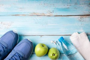 Flat lay sport shoes, bottle of water, apples, towel and earphones on blue wooden background