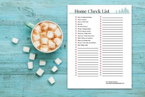 Cup of hot cocoa or chocolate with marshmallow and a home check list