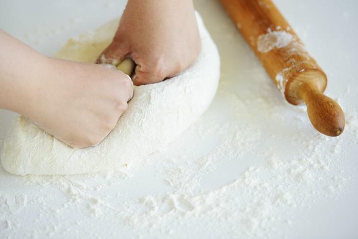 person kneading bread