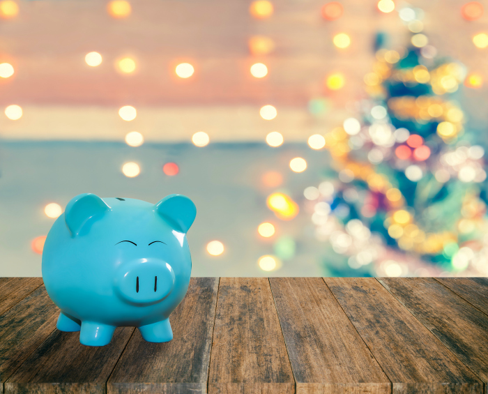 blue piggy bank in front of Christmas tree