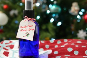 Candy Cane room spray in blue glass bottle in front of Christmas tree