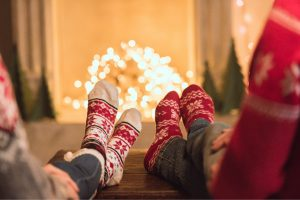 couple sitting in front of fireplace with christmas socks