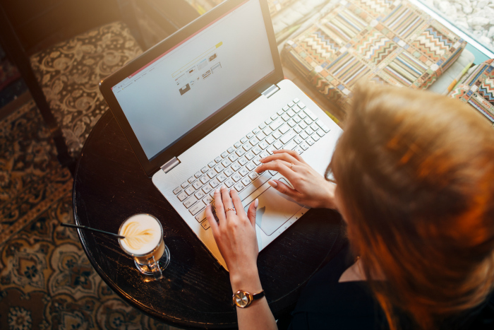 Overhead shot of woman on computer with coffee