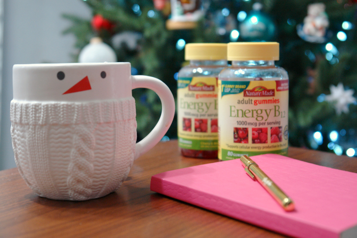 snowman mug, notebook, and vitamins in front of Christmas tree.