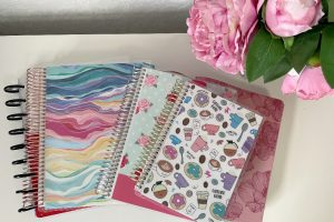 planners in a stack on a white table with pink flowers in vase